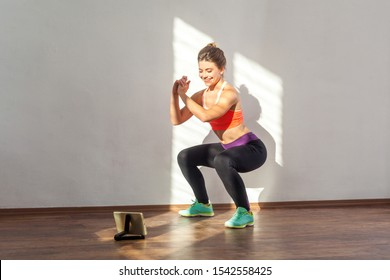 Positive sportive woman with bun hairstyle and in tight sportswear doing squatting sit-up exercise while watching training video on tablet. indoor studio shot illuminated by sunlight from window