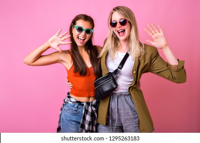 Positive studio indoor portrait of happy two best friends sisters hipster girls , happy emotions , screaming smiling and say hi, modern casual street style looks, vintage sunglasses.