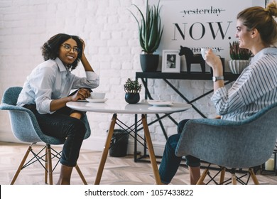 Positive stylish dark skinned girl enjoying tasty coffee and good communication together with best friend at home with cool interior.Two cheerful women talking about funny stories sitting at table