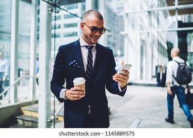Positive successful entrepreneur dressed in formal wear reading funny notification on smartphone from business partner.Cheerful proud ceo laughing while chatting online on phone during coffee break
