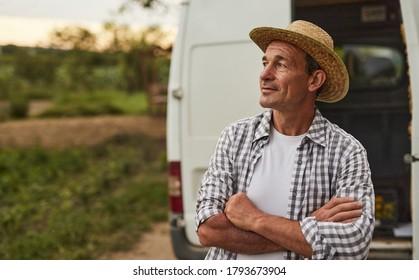 Erfolgreicher männlicher Kleinbauer mittleren Alters in karierten Hemden und Strohhut, der beim Stehen in der Nähe von LKW, beim Ernten und der Lieferung von Naturprodukten aus dem Feld wegschaut