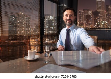 Positive sucessful businessman holding papers