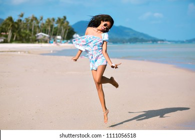 Positive summertime portrait of Asian stylish girl having fun on the beautiful tropical beach, trendy outfit and sunglasses, traveling vibes, amazing view on palms and mountains.