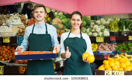 Positive supermarket workers offering fruits in vegetables section