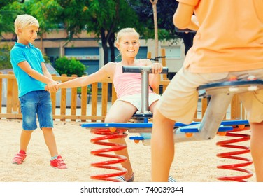 Positive swedish children are teetering on the swing in the playground.