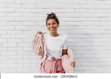 Positive tanned woman in white T-shirt puts on pink jacket. Portrait of lady with bun at background of white brick wall