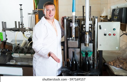 Positive technician of factory line posing near corking machinery in winery