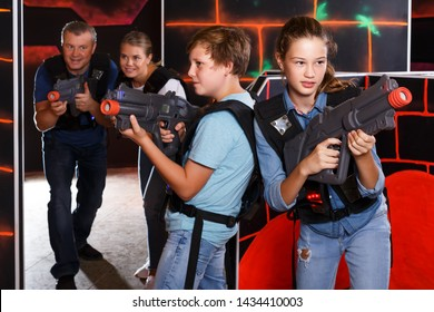 Positive teenage boy and girl with laser guns having fun with adults in dark lasertag room