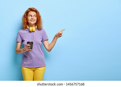 Positive teenage girl with red short hair, points away on free space, holds paper cup of coffee, has joyful smile, enjoys hot drink, wears casual outfit, makes choice and decides what to buy