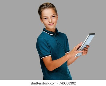The positive teenager boy holds tablet PC.