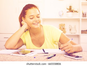 positive teenager girl taking notes while studying at home