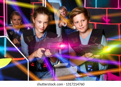 Positive  teenagers holding laser guns at other players during lasertag game with parents indoors