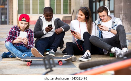 Positive teens playing on smarthphones and listening to music