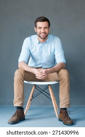 Positive thinker. Full length of handsome young man looking at camera and smiling while sitting against grey background