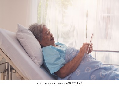 Positive thinking elderly patient with happiness,  is using the tablet on hospital bed, medicine, health care and old people concept