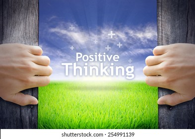 """""""Positive Thinking"""" Motivational quotes. Hands opening a wooden door then found a texts floating among new world as green grass field, Blue sky and the Sunrise."""
