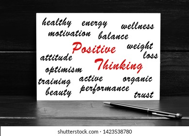 Positive thinking words on paper on a black wooden background