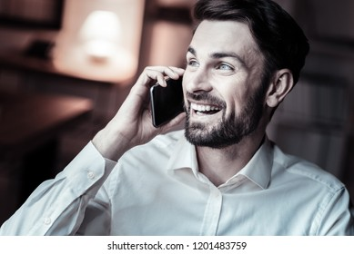 Positive thoughts. Cheerful bearded male person holding telephone near ear and smiling while talking