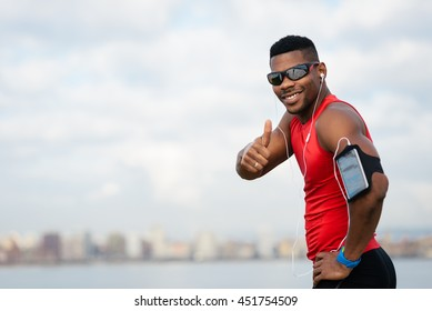 Positive urban black athlete celebrating running workout success towards city skyline background. Cheerful man doing successful thumbs up gesture.