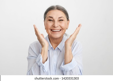Positive vibrations and human emotions. Pleased ecstatic lucky elderly Caucasian female in blue shirt expressing excitement and joy, smiling broadly, rejoicing at success, victory or life goals