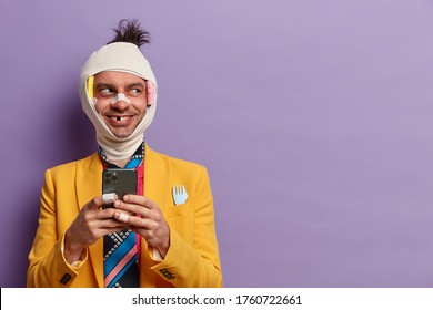 Positive victim of savage attack has hematoma, missing teeth and broken nose, holds smartphone in hands, spends rehabilitation period at home, wears yellow formal suit, isolated on purple wall