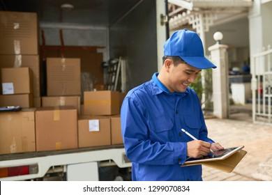 Positive Vietnamese courier signing document after delivering parcels