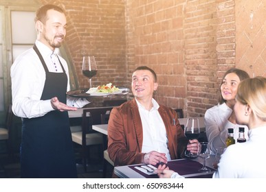positive waiter placing order in front of guests in country restaurant