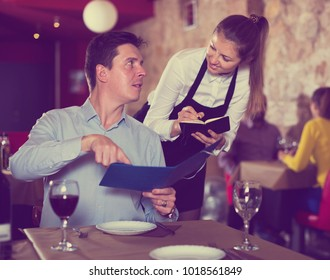 Positive waitress taking order from young man in restaurant, writing into note