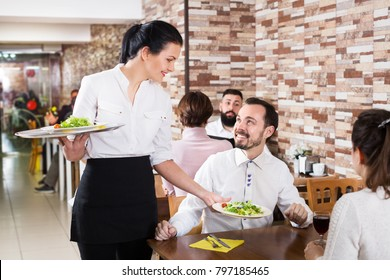 Positive waitress taking table order and smiling at the tavern