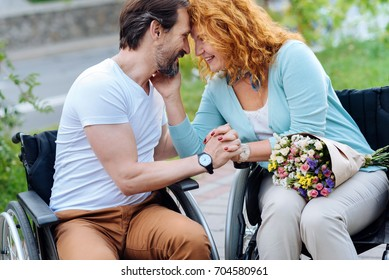 Positive wheelchaired senior couple expressing love