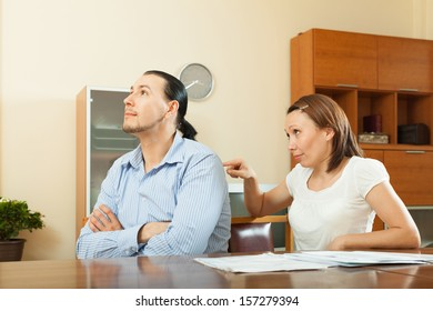 Positive woman asking for money from  husband for the purchase at home