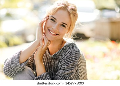 Positive woman with charming smile looks into camera. Girl in gray outfit posing on street in spring