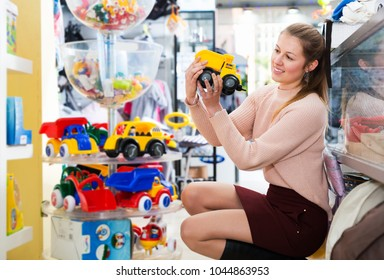 Positive woman in the children's store selecting assortment of plastic toys