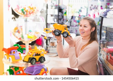 Positive woman in the children's store selecting different plastic toys