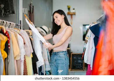 Positive woman choosing new clothes in shop and smiling