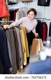Positive woman choosing turtleneck sweater in women`s cloths shop