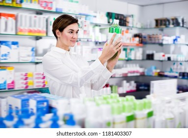 Positive woman customer browsing rows of drugs in pharmacy