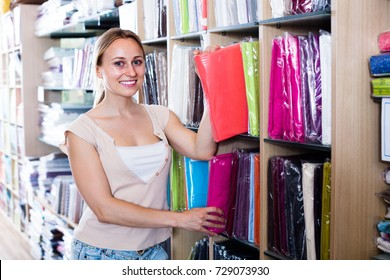 positive woman customer picking bedding set in package in textile department