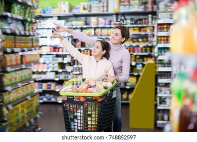 Positive woman with daughter shopping with shopping cart in supermarket