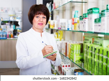 Positive woman druggist wearing white coat standing among shelves in pharmacy