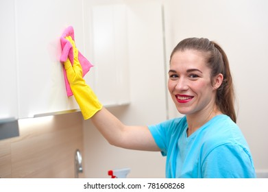 Positive woman employee of  cleaning company in gloves wipes furniture from dust with  rag