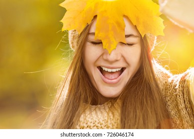 Positive woman face smiling and hide behind maple leaf