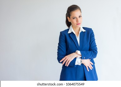 Positive woman in formal suit covering stomach with crossed arms. Portrait of female manager in early stage of pregnancy. Business and pregnancy concept