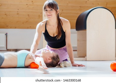 Positive woman instructor helping client doing self-massage technique applying franklin ball for shoulder blade pain relief, working out lying on floor in pilates studio with equipment on background.