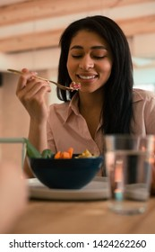 Positive woman looking at her meal with a smile while eating vegetable salad from the fork