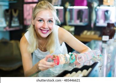 positive woman seller showing various bracelets in bijouterie boutique