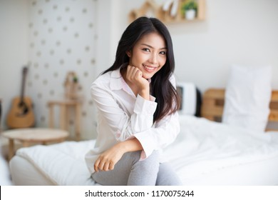 Positive woman sitting in bed and smiling to camera at home