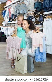 Positive woman with small daughter holding clothes in kids apparel store