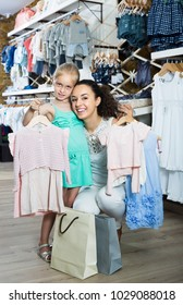 Positive woman with smiling girl holding clothes in kids apparel boutique