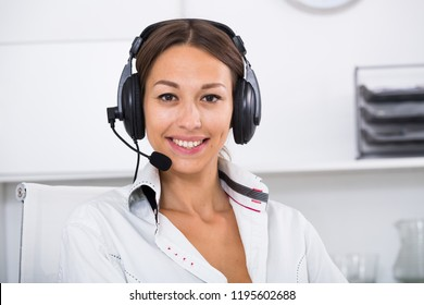 positive woman talking with customer using hands-free set at call center